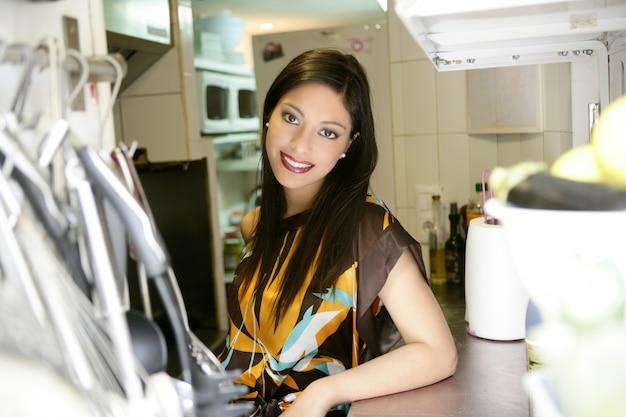 Mujer hermosa de la moda en la cocina
