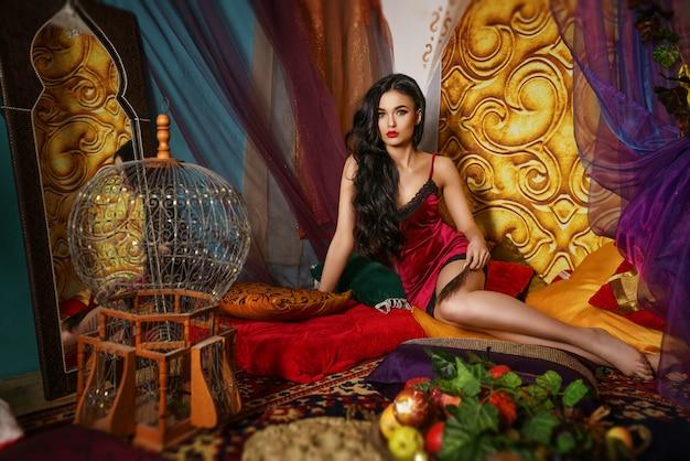 La mujer hermosa de moda miente en una bata roja