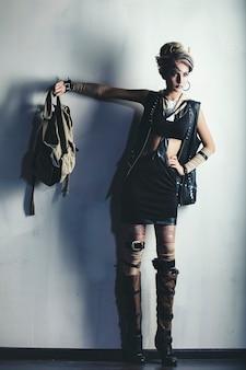 Mujer hermosa modelo con arte corporal en la cara de ropa inusual y de moda