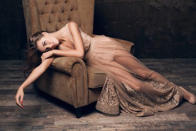 Mujer hermosa modelo sexy en vestido de noche de encaje brillante posando sentada en una silla de color beige