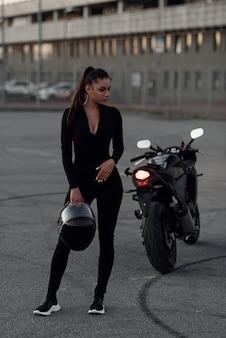 Una mujer hermosa del motorista que sostiene el casco próximo superbike fuera de un edificio.