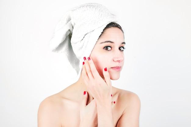 Mujer hermosa y natural joven envuelta en la toalla aislada sobre el fondo blanco