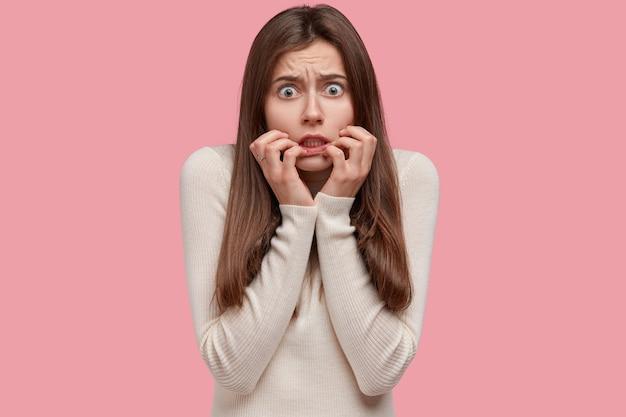 Mujer hermosa nerviosa tiene mirada preocupada, se siente desconcertada y estresada antes de la sesión de examen, mantiene las manos cerca de la boca, vestida con un jersey blanco