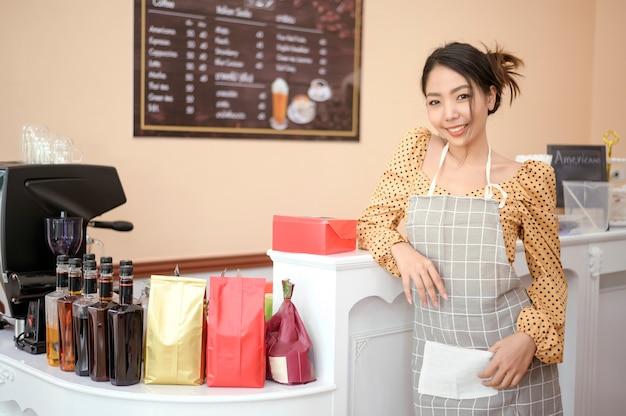 Una mujer hermosa panadería o dueño de una cafetería está sonriendo en su tienda