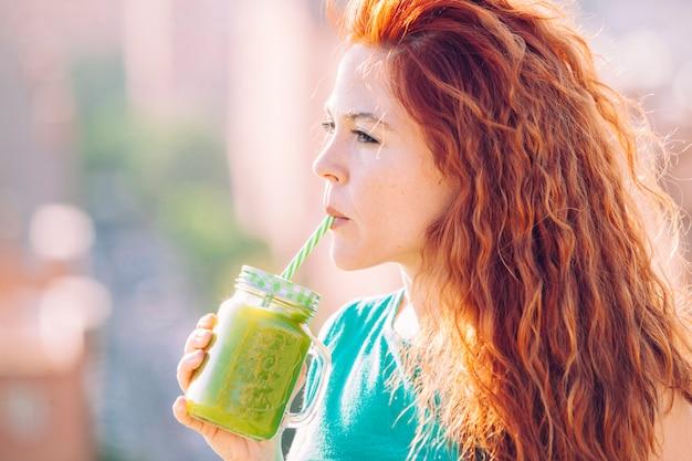 Mujer hermosa pelirroja bebiendo con una pajita un jugo verde saludable