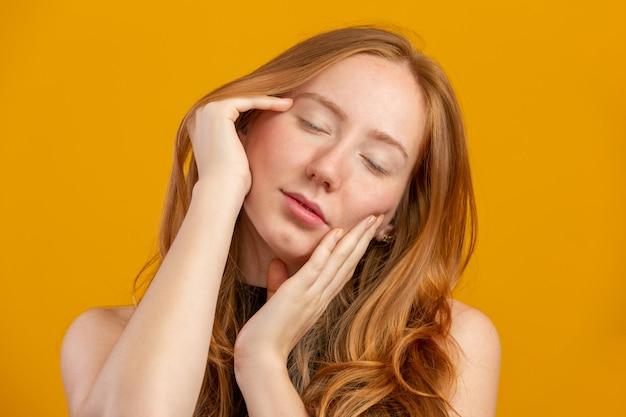 Mujer hermosa pelirroja. crema hidratante o imprimación facial. concepto de juventud y cuidado de la piel. tratamiento facial. concepto de belleza, cosmetología y cuidado de la piel. crema corporal.
