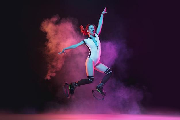 Mujer hermosa pelirroja en una ropa deportiva roja saltando en un kangoo salta zapatos sobre fondo oscuro.
