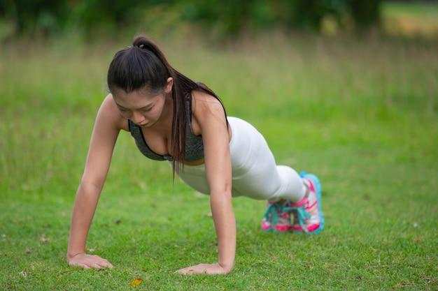 Mujer hermosa con el pelo largo que ejercita en el césped del parque.