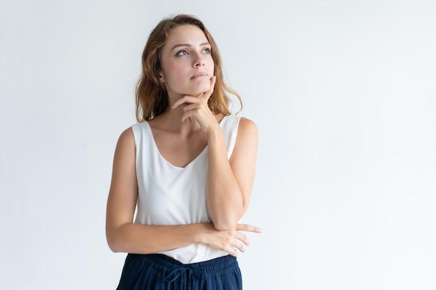 Mujer hermosa pensativa que toca la barbilla con los dedos