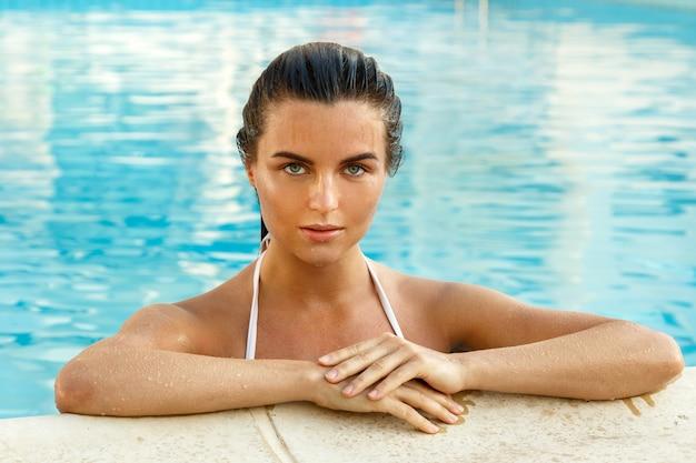 Mujer hermosa, en la piscina