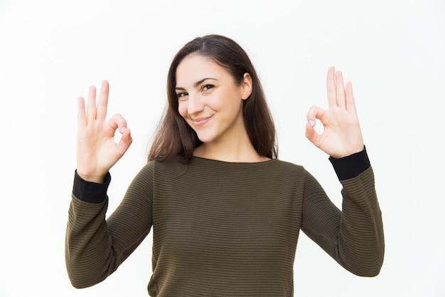 Mujer hermosa positiva alegre que hace gesto aceptable