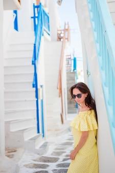 Mujer hermosa en el pueblo griego. mujer hermosa joven de vacaciones en mykonos