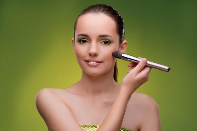 Mujer hermosa que aplica maquillaje en concepto de la belleza