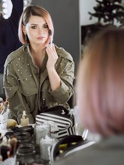 Mujer hermosa que aplica maquillaje
