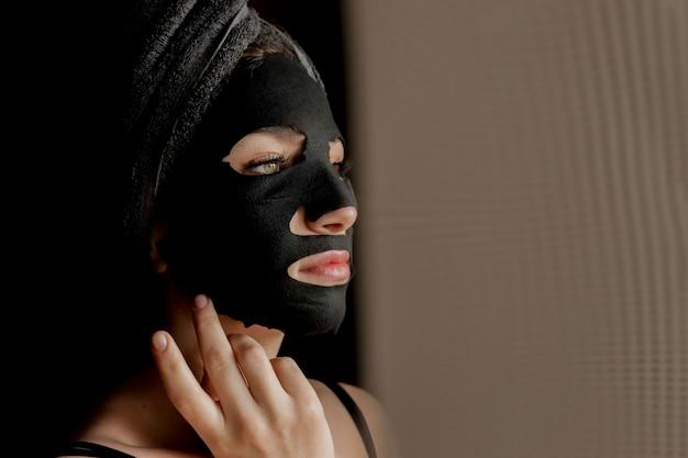 Mujer hermosa que aplica la máscara facial negra.