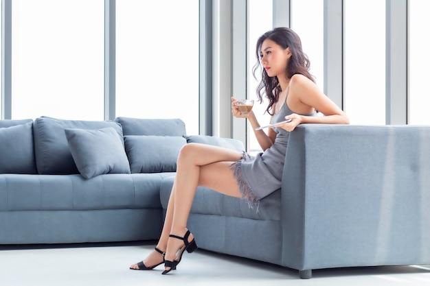 Mujer hermosa que bebe el café y que hace compras en línea con la tableta en sala de estar.