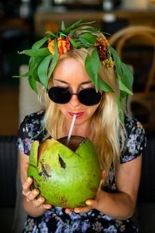 Mujer hermosa que bebe el coco en el café tropical