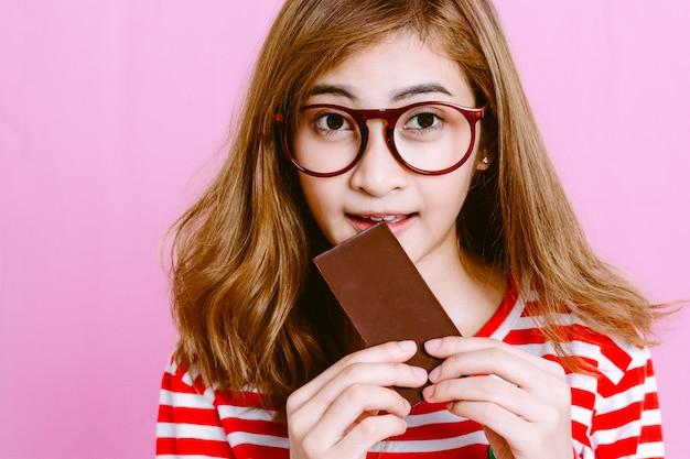 Mujer hermosa que come el chocolate oscuro en fondo rosado