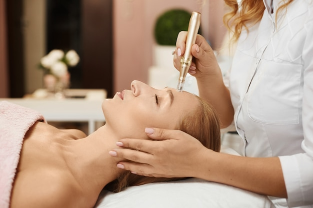 Mujer hermosa que consigue procedimiento de peladura de cara en una clínica de la belleza, retrato del primer. tratamiento facial rejuvenecedor.