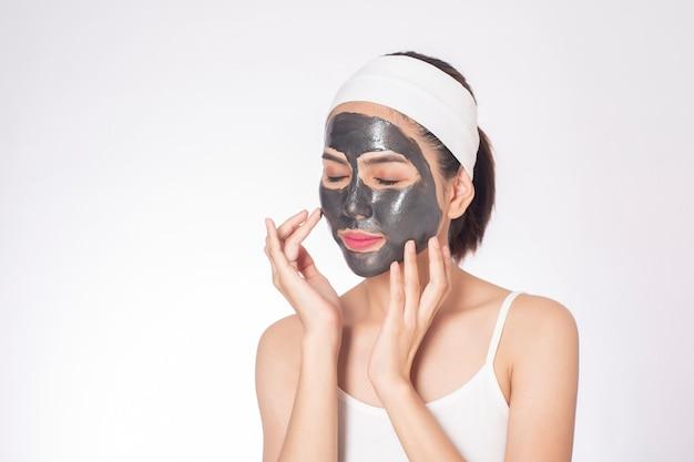 Mujer hermosa que enmascara su cara en el fondo blanco