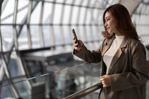 Mujer hermosa que espera vuelo y que usa el teléfono elegante en aeropuerto