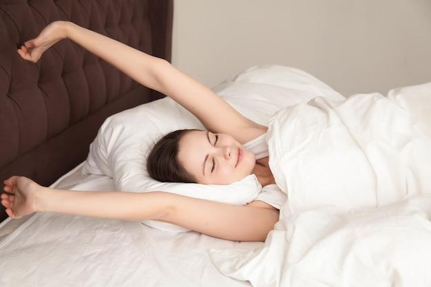 Mujer hermosa que estira con placer en cama