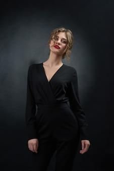 Mujer hermosa que lleva el traje negro que presenta en fondo gris del estudio.