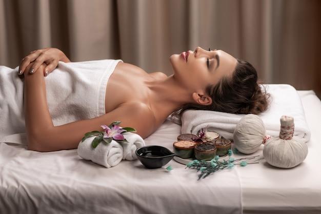 Mujer hermosa que miente con humor feliz el día de vacaciones. concepto de bienestar corporal y aromaterapia spa.