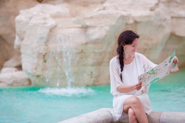 Mujer hermosa que mira el mapa turístico de la ciudad cerca de la fuente de trevi, roma, italia.