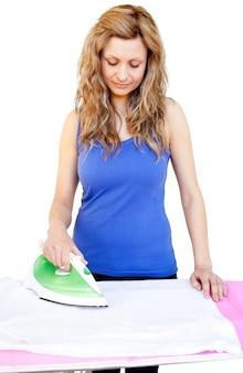 Mujer hermosa que plancha su ropa contra el fondo blanco