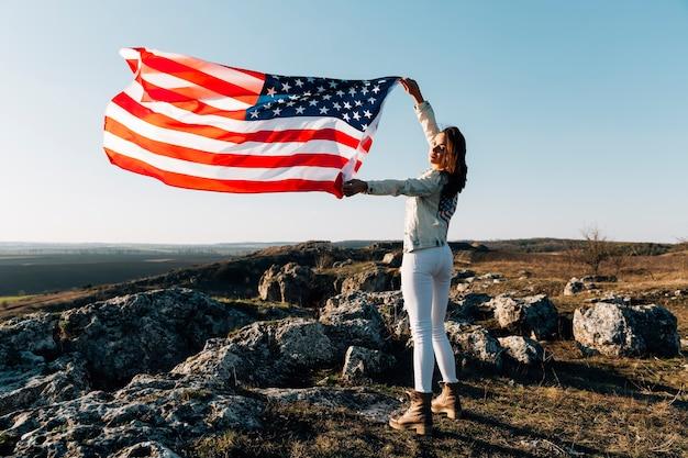 Mujer hermosa que presenta con la bandera americana encima de la montaña