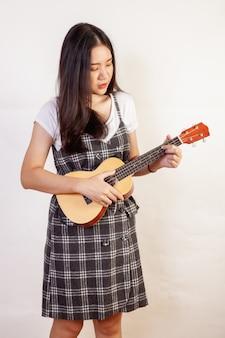 Mujer hermosa que presenta tocando el ukelele en una pared blanca.