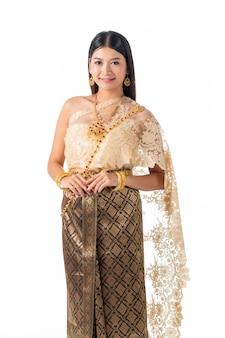 Mujer hermosa que sonríe en el traje tradicional nacional de tailandia.
