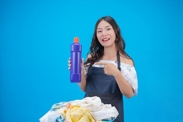 Mujer hermosa que sostiene el detergente para ropa preparado en azul