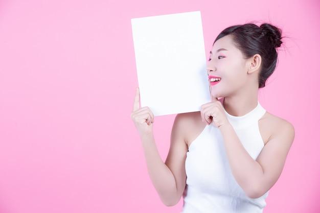 Mujer hermosa que sostiene una hoja del tablero blanco en un fondo rosado.
