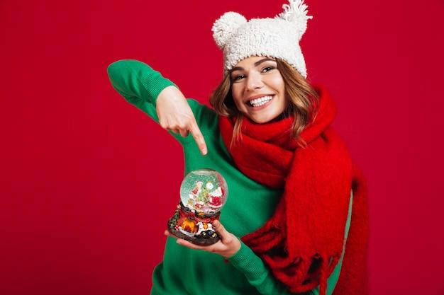 Mujer hermosa que sostiene el juguete de la navidad