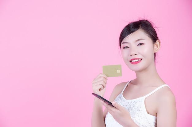 Mujer hermosa que sostiene un smartphone y una tarjeta en un fondo rosado