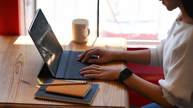Mujer hermosa que trabaja en la pantalla en blanco de la tableta de la computadora mientras que se sienta en la mesa de trabajo de madera.