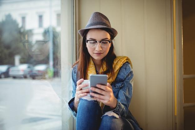 Mujer hermosa que usa el teléfono celular en el café