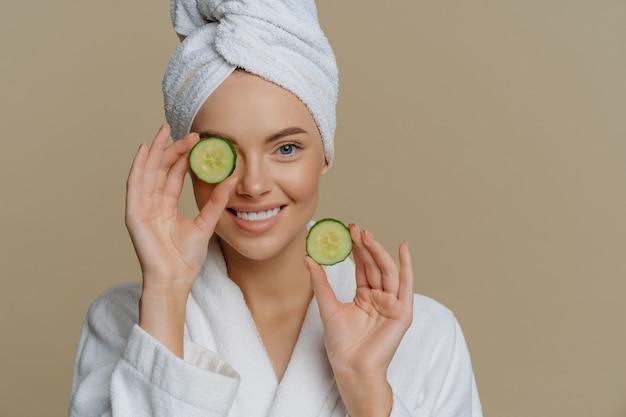 Mujer hermosa refrescada positiva sostiene rodajas de pepino fresco hace mascarilla para la piel de la cara