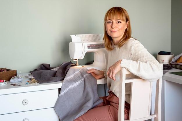 Mujer hermosa sastre con máquina de coser