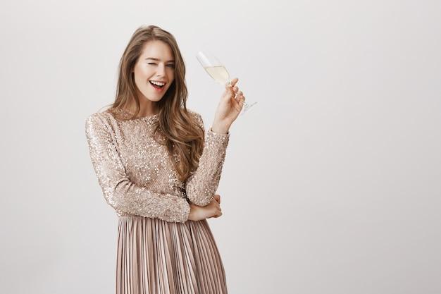 Mujer hermosa sonriente que bebe champán en la fiesta
