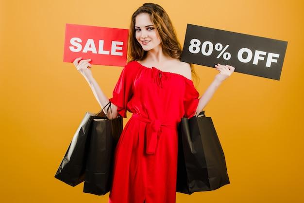 La mujer hermosa sonriente tiene venta muestra del 80% del descuento con las bolsas de compras coloridas aisladas sobre amarillo