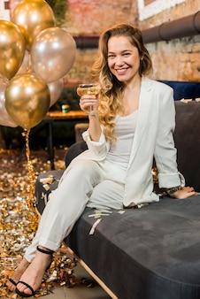 Mujer hermosa sonriente con el vidrio de whisky que se sienta en el sofá