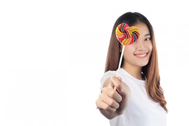 Mujer hermosa con una sonrisa feliz que celebra un caramelo de la mano, aislado en el fondo blanco.