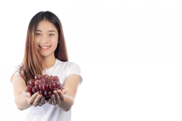 Mujer hermosa con una sonrisa feliz que celebra una uva de la mano, aislada en el fondo blanco.