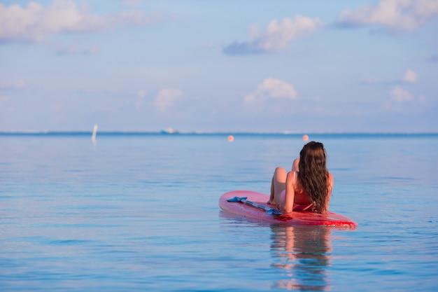 Mujer hermosa surfista surfeando en el mar turquesa durante las vacaciones de verano
