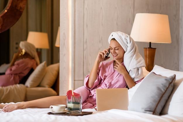Mujer hermosa con la toalla en la cabeza que habla en el teléfono en dormitorio en casa. rutina de la mañana.