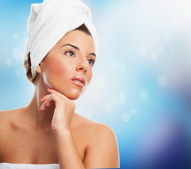 La mujer hermosa en una toalla con la piel perfecta