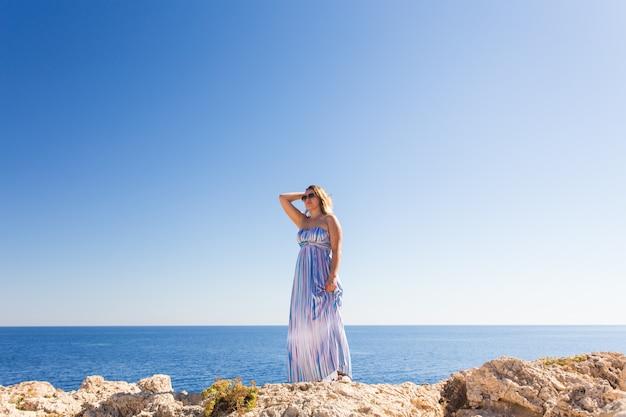 Mujer hermosa en un vestido rayado que camina en la playa. mujer relajada que respira el aire fresco, mujer sensual emocional cerca del mar, disfrutando del verano. viajes y vacaciones. concepto de libertad e inspiración.